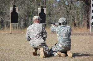 Cpt. Freeman of the Army Reserve Marksmanship Program (left) coaches a Soldier at the USACAPOC Small Arms Championships March 22 at Fort Bragg.